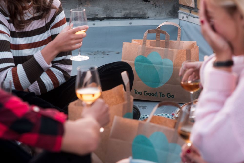 people holding wine glasses with too good bags