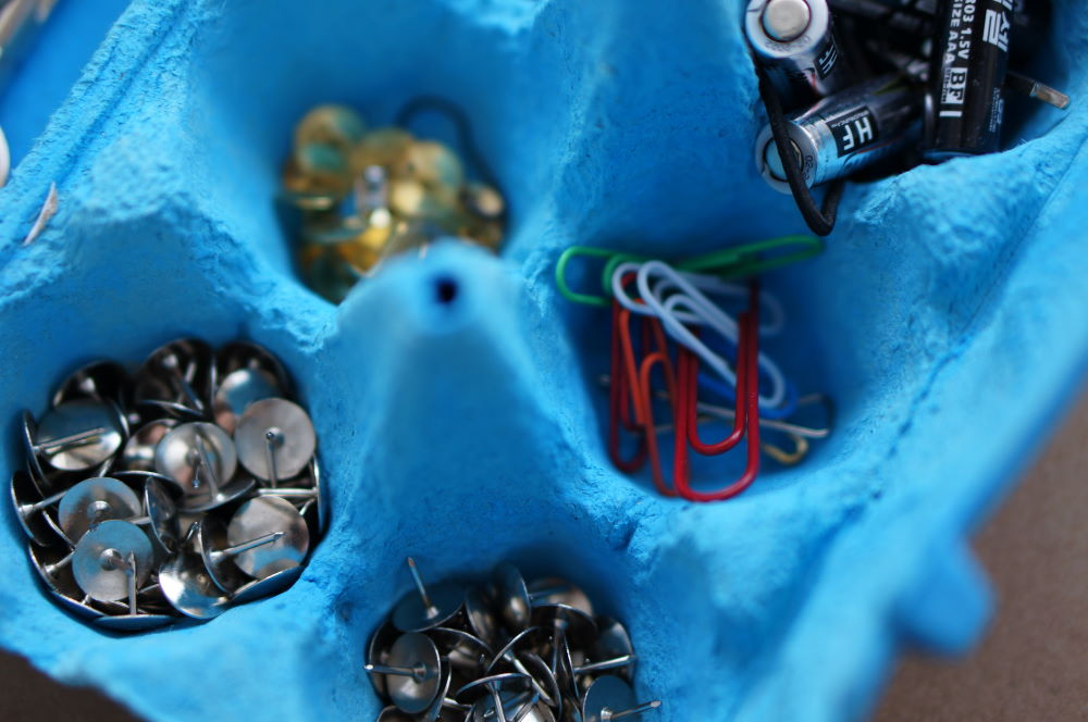 Egg carton with clips, stud nails and batteries