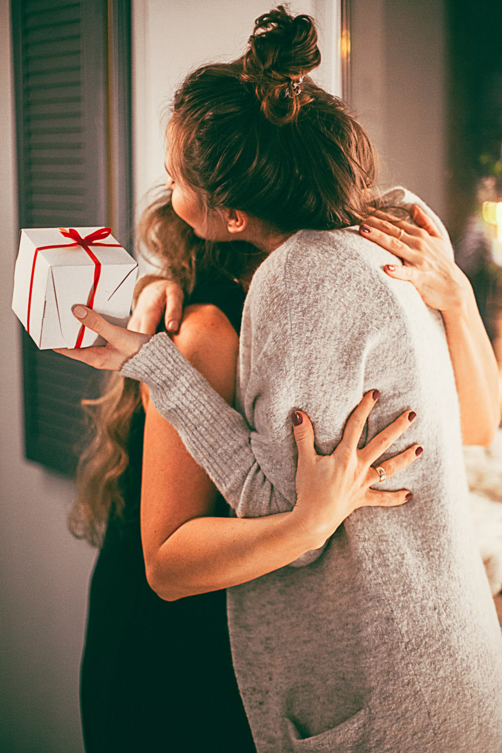 two women hugging each other, one with present on her hand
